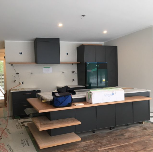interior of a kitchen during a renovation with dark cabinets being installed and many exposed wires