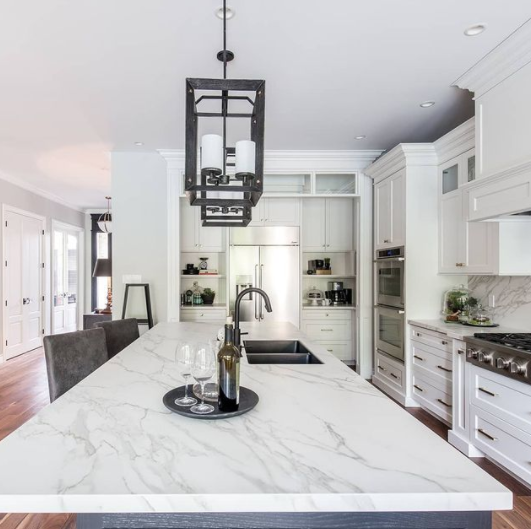 interior of a recently renovated kitchen with many white details and dark accents featuring a large island