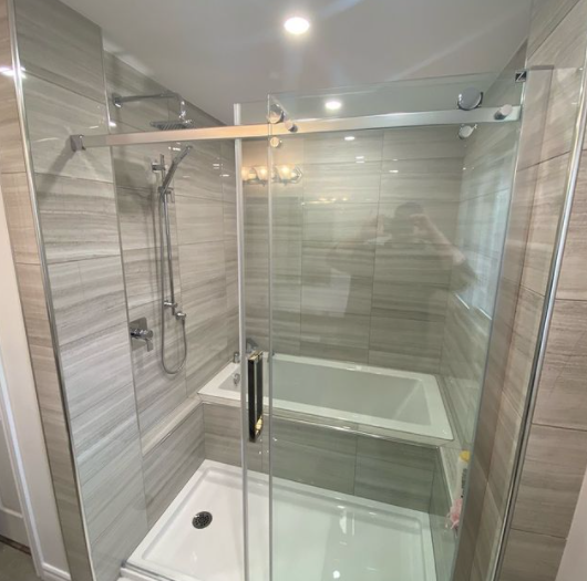 interior of a recently renovated bathroom shower with tanned colour tiles in the shower and stainless steel detailing