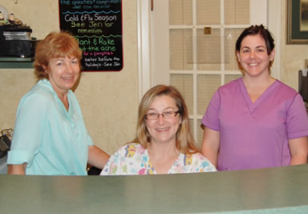 three women behind a medical office desk smiling at the camera