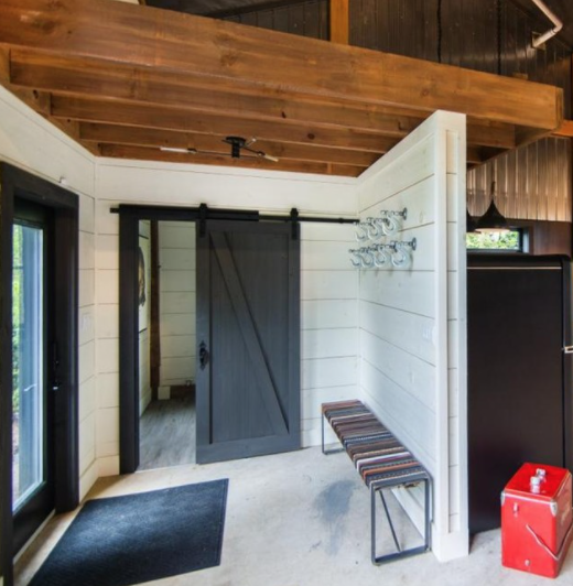 home entryway that has been renovated featuring a large barn door beside the front door and many beams above