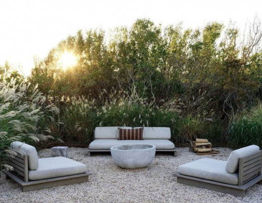 a backyard living set with grey couches sitting on a bed of pebbles surrounded by leafy plants