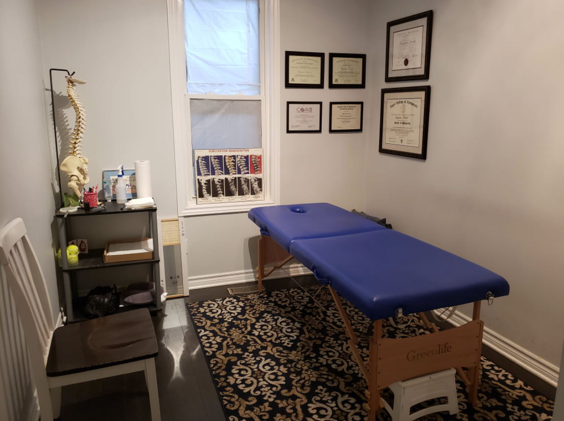 interior of a medical room with a blue massage table and chair on the other side
