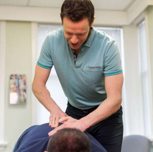 man cracking another mans back that is face down on a massage table