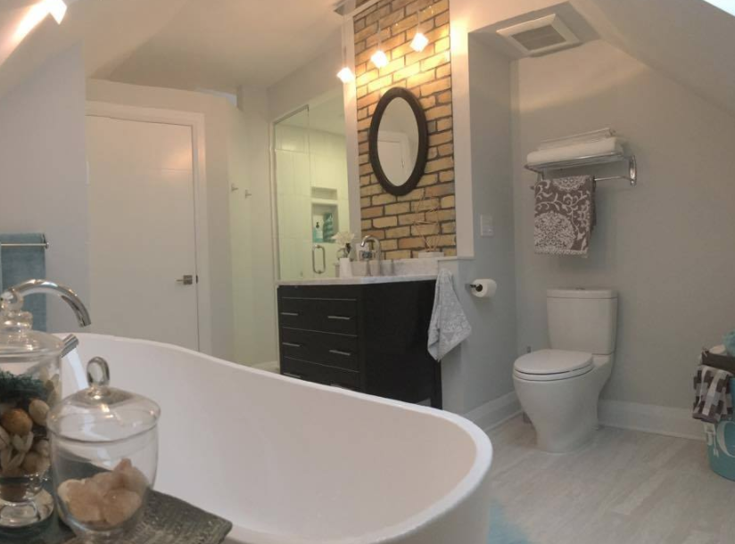 interior of a large bathroom with one exposed brick wall and many light accents throughout the room