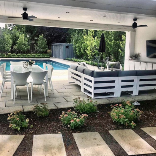 large backyard pool cabana with concrete stone walkway beside a garden with flowers and a large lounge area in behind