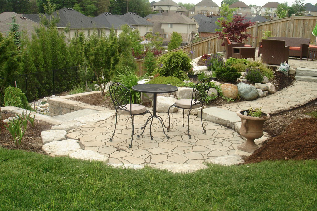 a large backyard oasis with two different patio sets on different levels amongst many plants and flowers