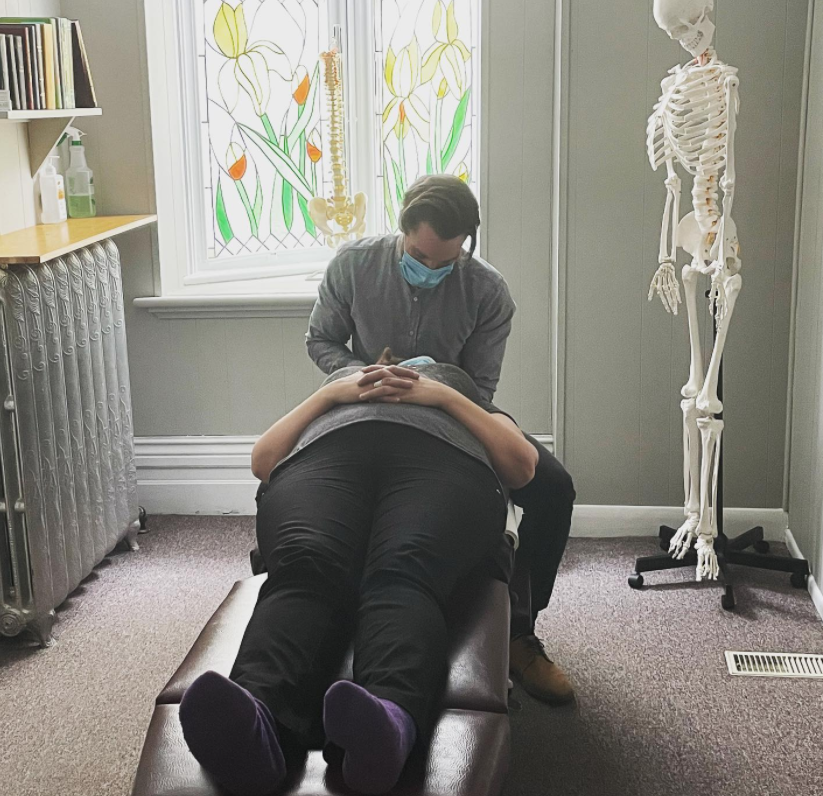 woman laying face up on a massage table with man by her head performing medical task with a skeleton in the backround