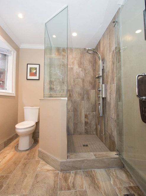 interior of a bathroom that was recently renovated with many brown details with stainless steel hardware in the shower