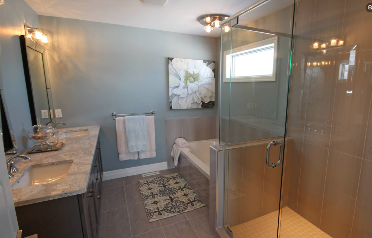 interior of a recently renovated bathroom with various colours throughout the room and all the lights on