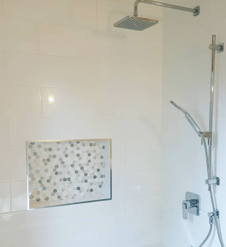 interior of a recently renovated shower with hexagon tile accent and silver hardware