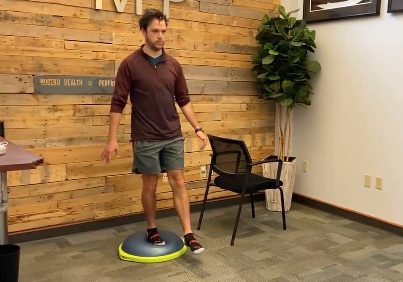 man standing on a balance ball with one foot off beside a chair for support