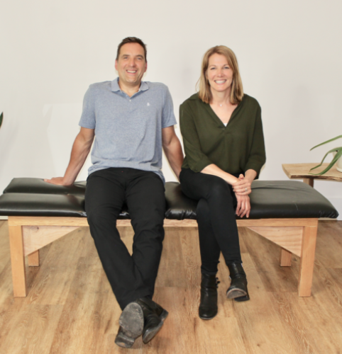 two chiropractors sitting on a massage table smiling at the camera