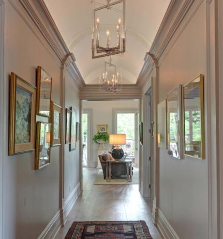 home hallway that was recently renovated with many pictures hanging on the wall and a large chandelier hanging from the ceiling facing a window