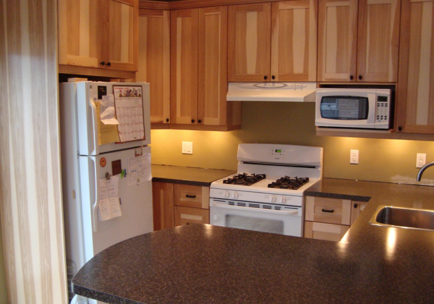 a kitchen that was recently renovated with wooden cabinets, older white appliances, and a speckled countertop