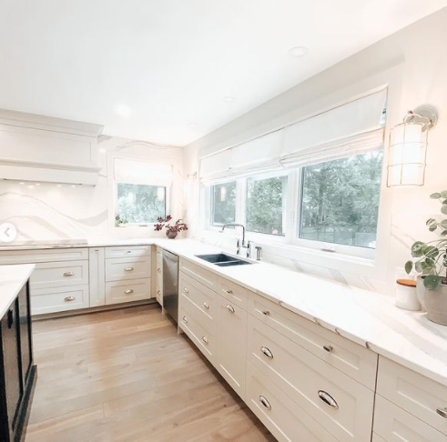 large white kitchen with stainless steel accents and large window near the sink and other wall