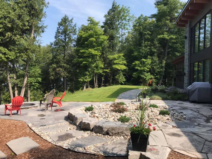 view of backyard with large stone walkway leading to patio set with various shrubs and flowers throughout