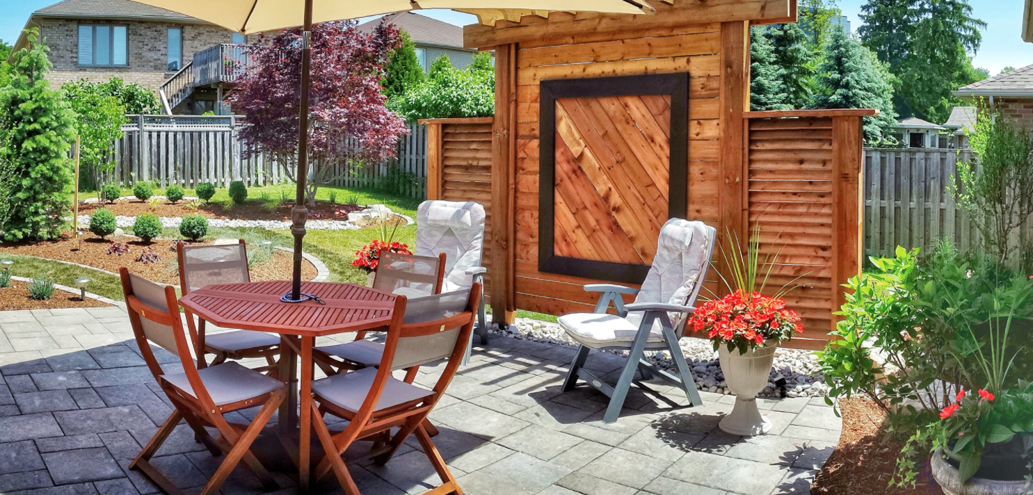 backyard seating area with a small shade structure and many manicured gardens in behind