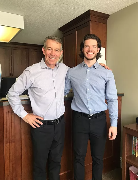 two men smiling at camera inside a medical office wearing suits