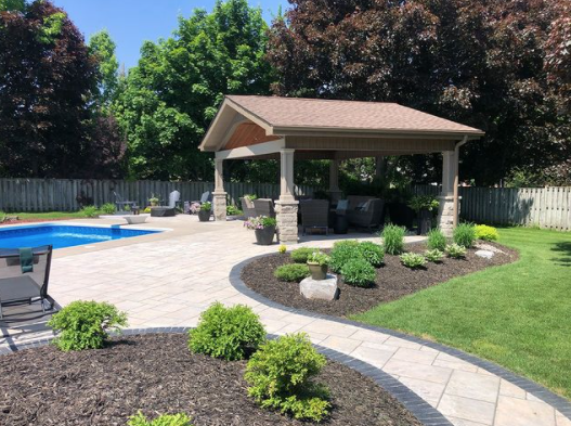 large pool cabana in a backyard with a stone walkway leading to pool and a sun shade on top of the patio set