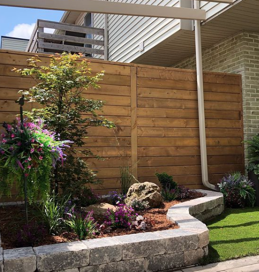 freshly manicured garden with various small trees, plants, and shrubs sitting in front of a new fence