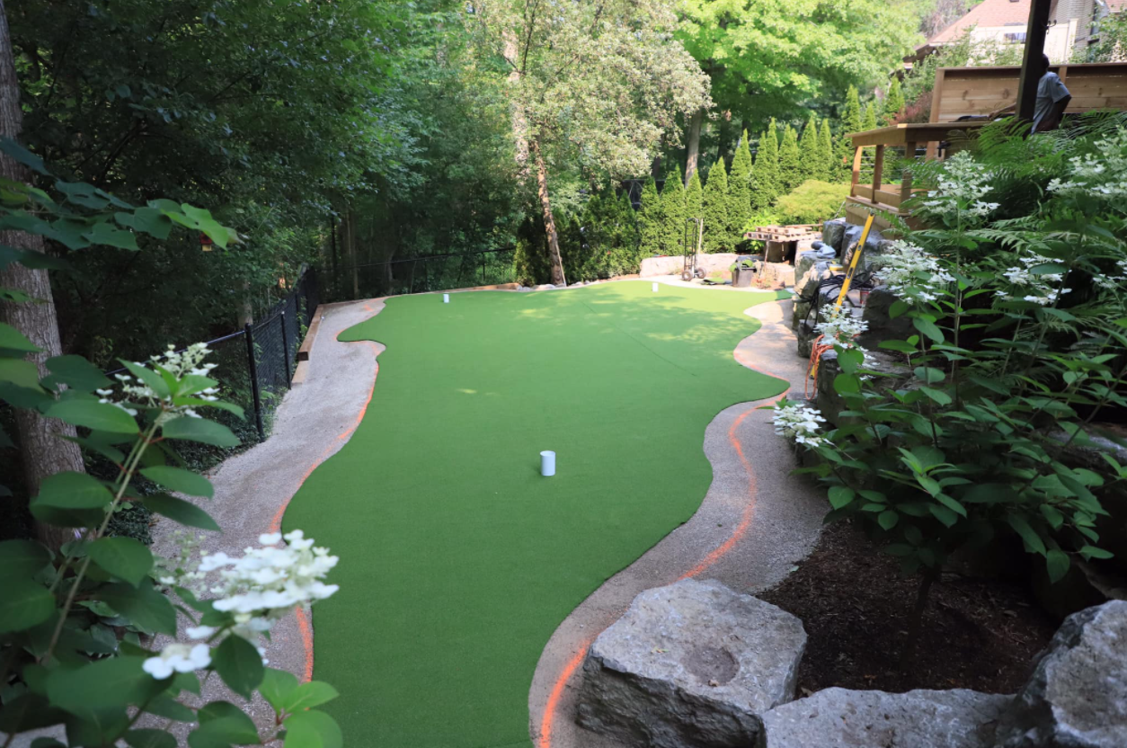 large backyard mini putt green surrounded by rocks and beautiful garden with white flowering plants on the right
