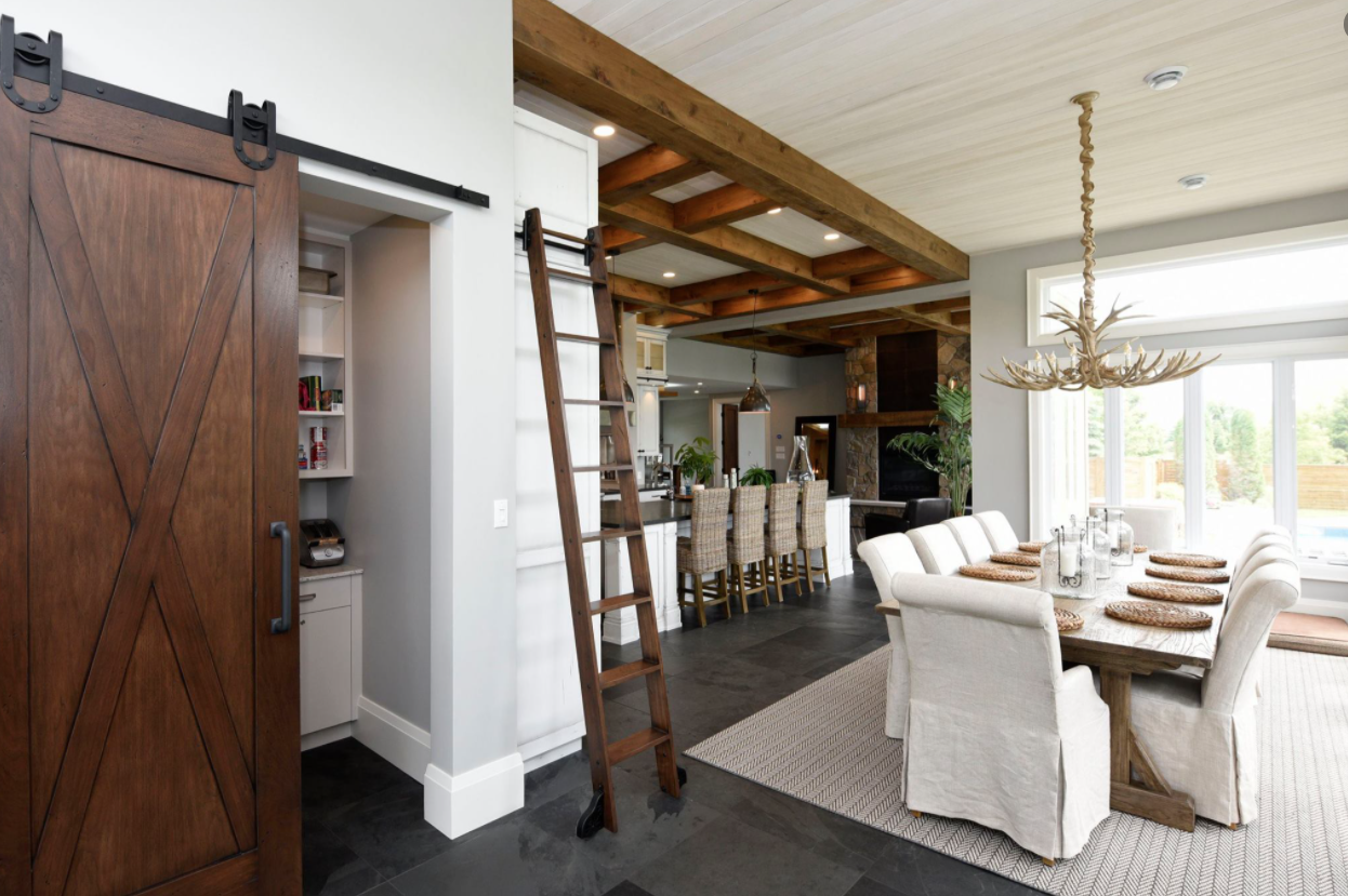 recently renovated dining room featuring a large brown barn door, rolling ladder, antler style chandelier and many wood beams on the ceiling (open concept)