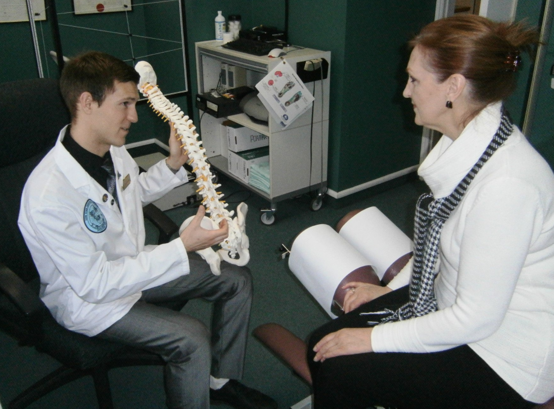 man in a white lab coat holding a spine model pointing at something to a woman sitting on a massage table