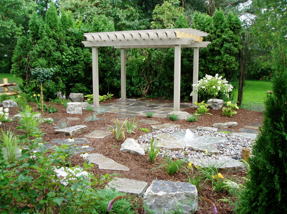 large garden gazebo with various pieces of stone for a walkway and plants, shrubs, and flowers throughout