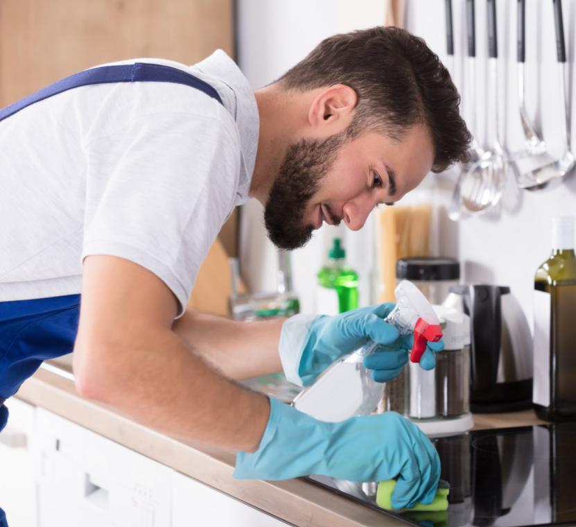 man wearing apron scrubbing a stovetop holding a spray bottle