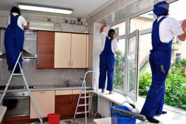 three people wearing blue coveralls standing on a counter scrubbing various parts of a kitchen