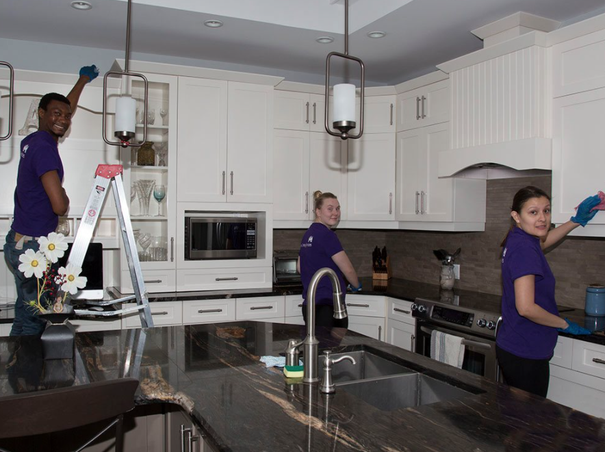 three cleaners in purple shirts all looking at camera holding various cleaning products and supplies