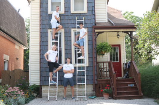four employees looking at camera about to clean the exterior of a house