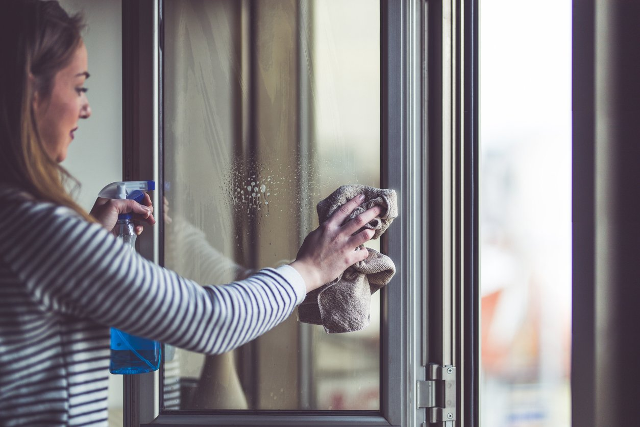 Young woman cleaning window glass at home