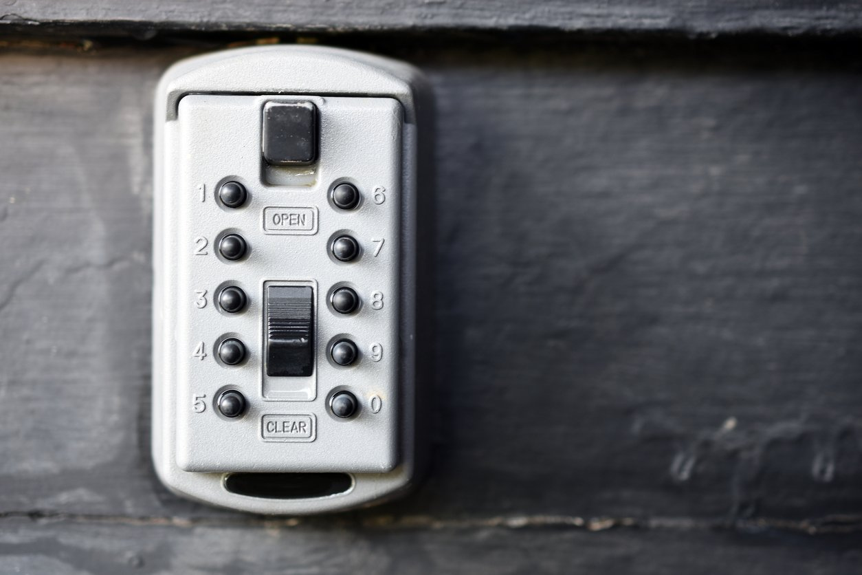 A close up image of an exterior lock box designed to hid a spare key.