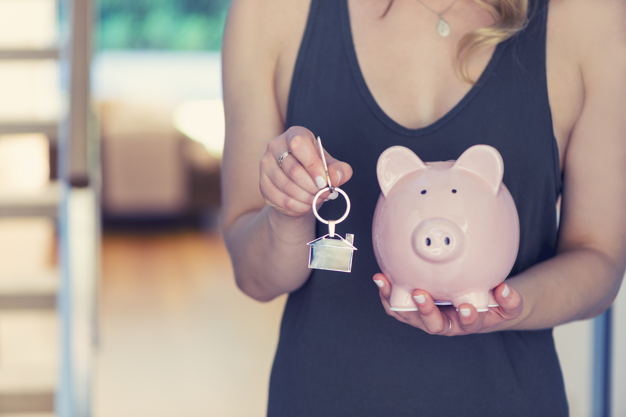 Woman holding house keys and a piggy bank. The key ring is house shaped. There is a home interior in the background. Home ownership and savings concept. Copy space.