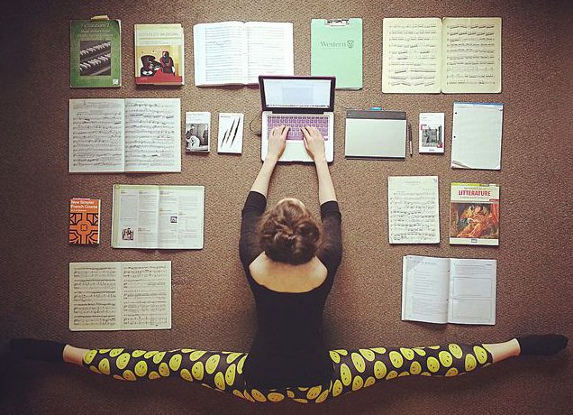woman doing splits while studying with laptop and textbooks all around