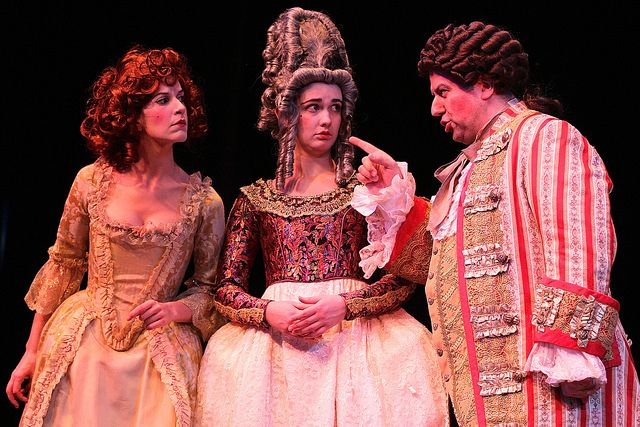 three actors dressed in Shakespearian clothing with man pointing to the left