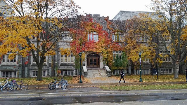 exterior of old grey stone building in fall with person walking past