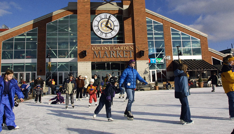exterior of market with an outdoor skating rink and many people skating