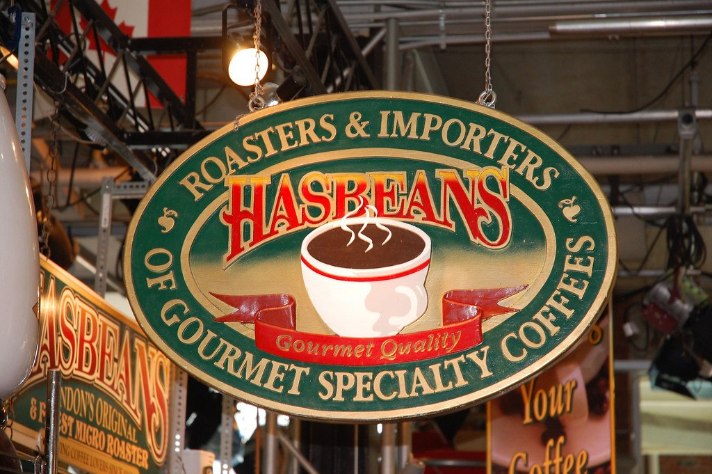 market sign with green and red accents featuring a coffee cup