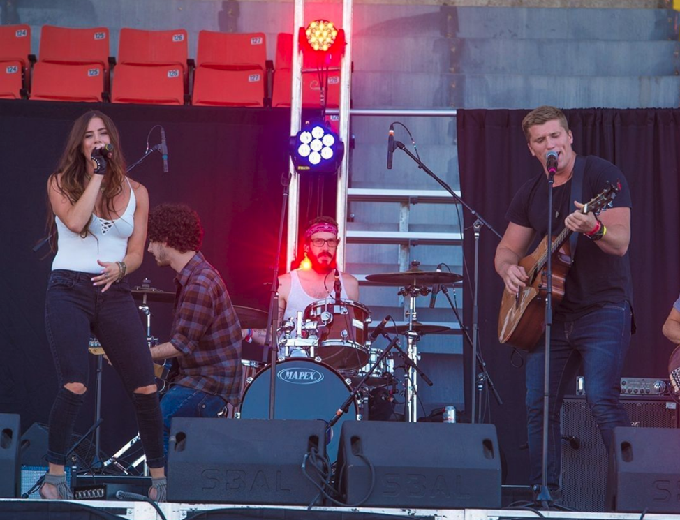 four people performing on stage with red and blue lights with two people In front and people in background playing instruments