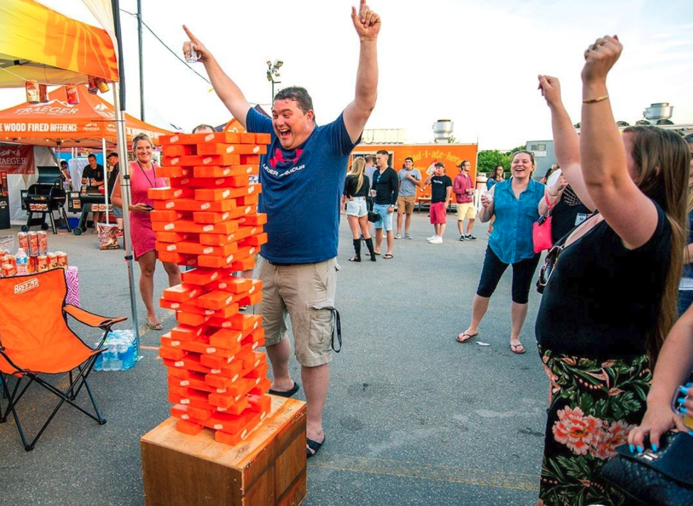 man at vendor tent playing orange giant jenga with arms raised beside woman with arms raised