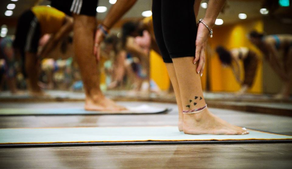 view of people calf down on yoga mats holding shins facing mirror