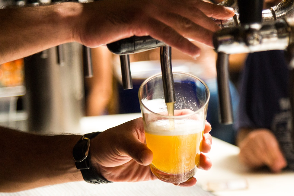 person holding draught beer glass towards open tap and pouring light coloured beer