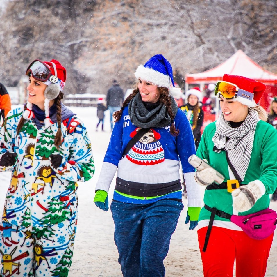 3 women in christmas sweaters and hats outside looking to the left of camera