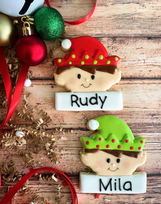 decorated elf cookies with names and ornament decor to the left