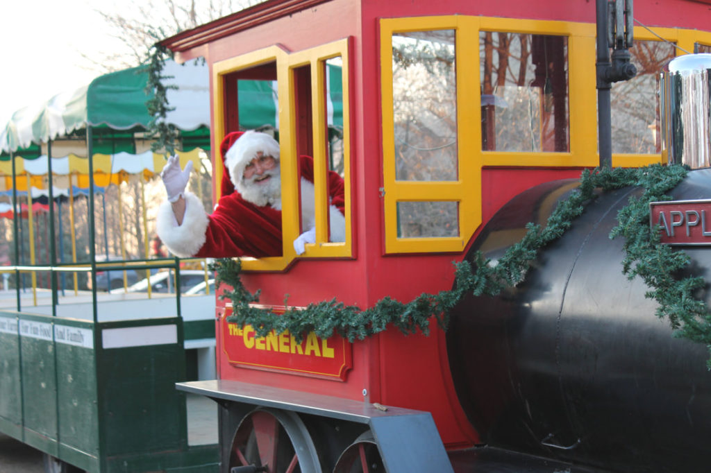 santa clause sticking his head out of a christmas train and waving