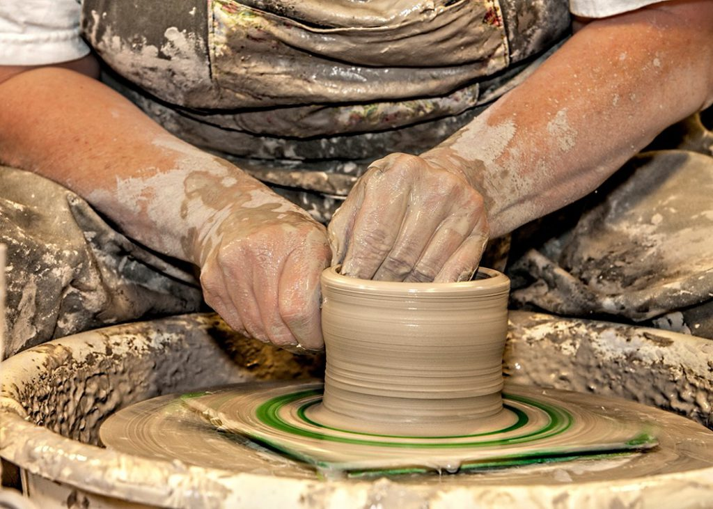man sitting at pottery station holding loose clay forming pot