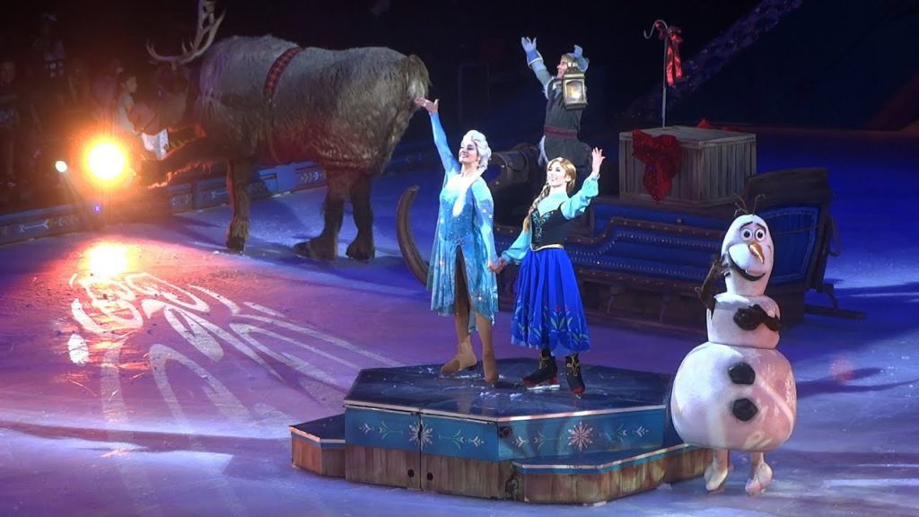 disney on ice frozen performers on platform waving towards crowd with snowman skating around